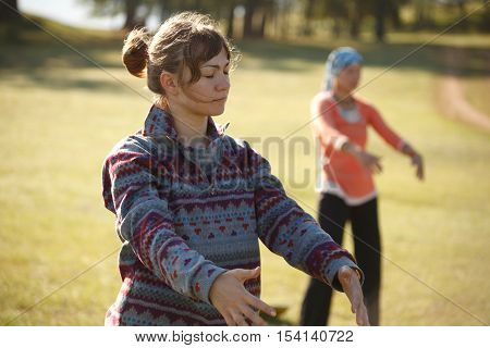 Two women are practicing Qi Gong in the moning