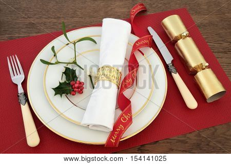 Christmas dinner table setting with white porcelain plates, knife and fork, linen serviette, red ribbon, holly, mistletoe and cracker over oak background.