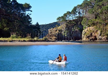 Couple rows a rubber inflatable dinghy boat to Roberton Island in the Bay of Islands New Zealand.