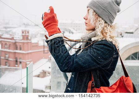 Young blond curly smiling female in warm clothes red gloves and bag standing on the roof and shooting on retro film camera, background of winter city, snow