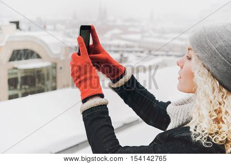 Young blond curly female tourist in warm clothes and red gloves making selfie or photo standing on the roof of winter city