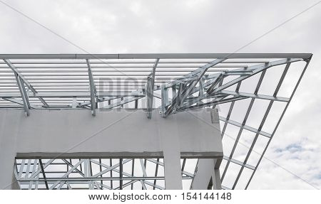 Structure of steel roof frame with blue sky and clouds at construction site