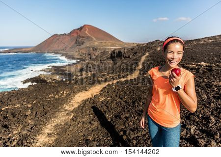 Happy hiker hiking on mountain trail path taking a break eating a healthy snack - apple fruit. Fitness woman runner on trail running training enjoying organic food in mountains landscape.