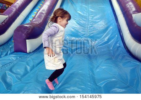 Little Girl Plays On Inflatable Giant Slide