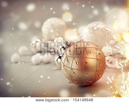 Christmas Bauble over blurred Background. Golden Holiday Abstract Glitter Defocused Background With Blinking Stars. Traditional Christmas decoration over Blurred Bokeh