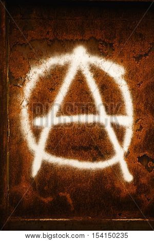 Anarchy symbol graffiti spray painted on grunge corroded metal wall