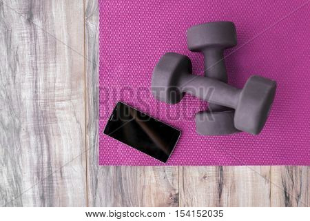 Fitness at home: free weights, yoga mat, mobile phone app. Dumbbells on pink exercise mat and smartphone for training program health progress app. Mobile screen copy space for online exercise videos.