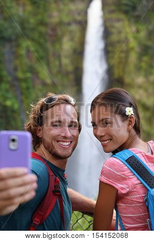 Hawaii couple tourists taking travel phone selfie self portrait with camera phone on Hawaii, Big Islands, Akaka Falls. Happy cheerful young multicultural couple on travel.