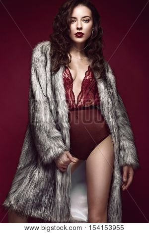 Beautiful sexy long-haired brunette woman in red lingerie and fur coat posing in the studio. The beauty of the face and body. Photos shot in a studio