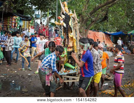 KOLKATA, INDIA - OCTOBER 11, 2016: Men carry Durga idol for immersion in the Ganges river. The idol immersion in the marks the end of the five day durga puja in West Bengal.