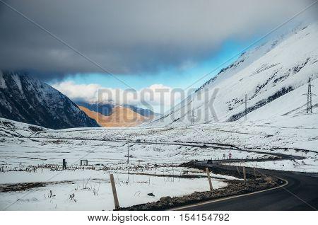 Georgian military road. The scenic winding road among the mountains in Georgia. Main Caucasian Ridge and Cross Pass Gudauri in winter.