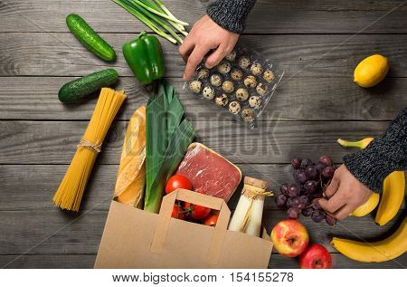 Man looks brown paper bag full of different healthy food on wooden kitchen table top view
