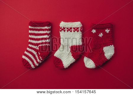 Mini Christmas Stockings.Three red and white wool Christmas stockings side by side.