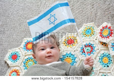 An Israeli newborn baby holding the Israeli flag. Concept photo Israel Israeli citizen patriotism family childhood fertility rate.