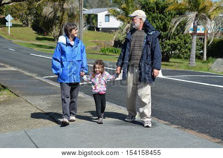 Young grandparents hold hand and walking with their granddaughter outdoor during the autumn.