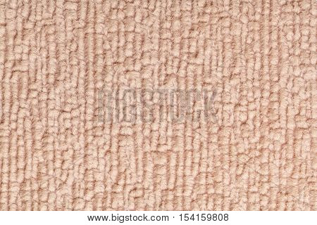 Light brown fluffy background of soft fleecy cloth. Texture of textile closeup