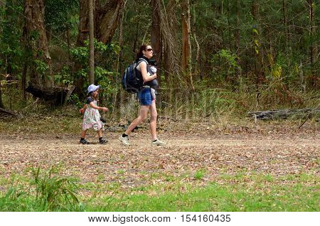Mother hike outdoor with her child (girl age 04) and her infant baby in the nature .