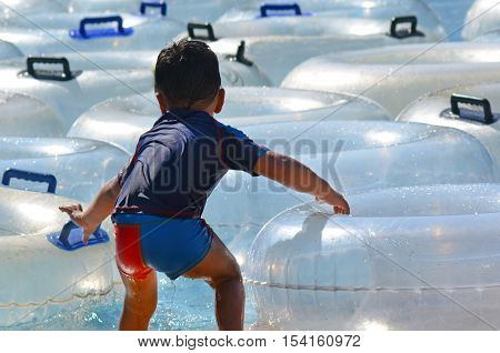 Child (Boy age 2) play with Inflatable clear inner tubes floating in clear blue waters
