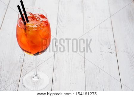 Spritz Aperol cocktail in wine glass on rustic wooden background.