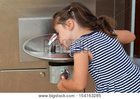 Little girl (age 04) drink water from outdoor water fountain.