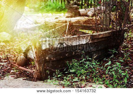 Last place of old broken boat in autumn garden.