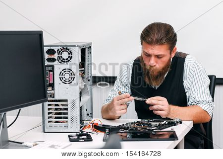 Repairman examine inside part of computer. Engineer looking at circuit of disassembled CPU in repair shop. Electronic renovation, fix, development concept