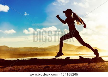 Silhouette of active healthy lifestyle athlete runner running in morning sunrise. Woman trail running on sunset ocean landscape sprinting with energy and speed in outdoor nature training cardio.