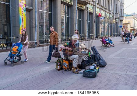 MOSCOW RUSSIA - MAY 10 2015: The street musician in Arbat street plays guitar and tambourine on his leg on May 10 in Moscow.