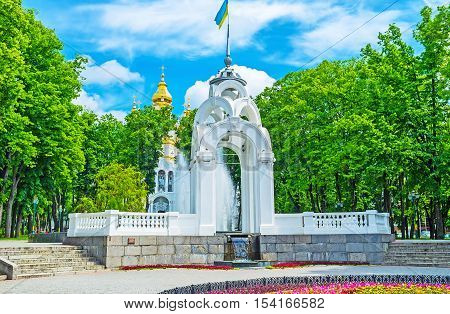 The scenic white alcove in Victory Square with the Mirror Fountain and bright gilt domes of the Church of Holy Myrrh-Bearers on the background Kharkov Ukraine.
