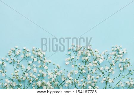 Wedding flower frame on blue table from above. Flat lay style.
