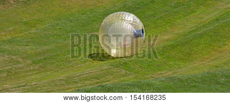Woman rides in ball rolling Zorbing in Rotorua New Zealand.