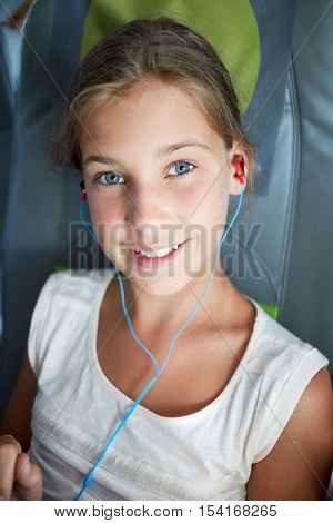 Portrait of teenage girl who listen to music through headphones sitting in armchair at plane.