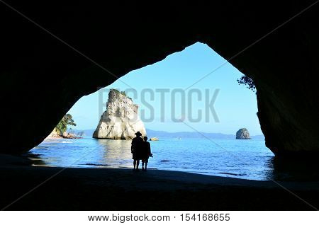 Silhouette of a couple visit in Te Whanganui-A-Hei (Cathedral Cove) Marine Reserve in Coromandel Peninsula North Island New Zealand.