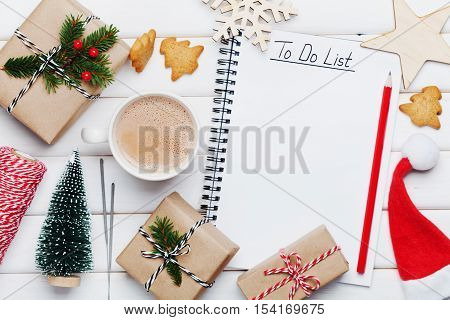 Cup of hot cocoa, holiday decorations, gift or present, miniature fir tree and notebook with to do list. Christmas or winter planning concept. Flat lay style.