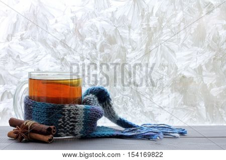 lemon tea in a transparent mug with a warm scarf and cinnamon sticks against the window with frosty patterns / Christmas hot drink for the winter holidays