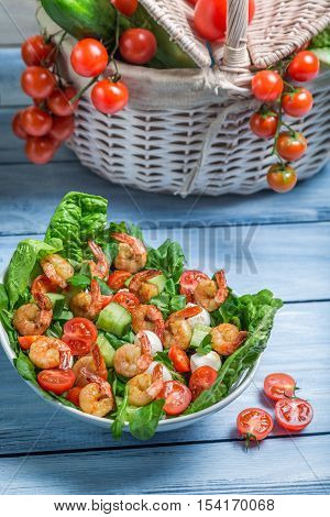 Healthy salad with shrimp and vegetables on old wooden table