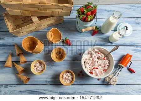 Homemade production of strawberry ice cream on old wooden table