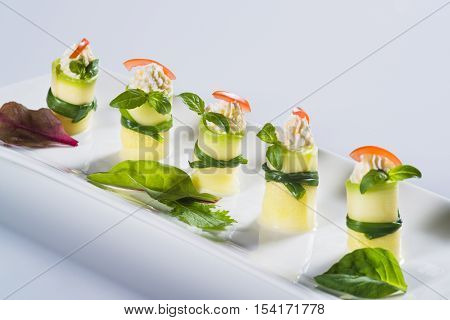 Beautifully decorated fresh squash rolls with soft cheese on plate on light background