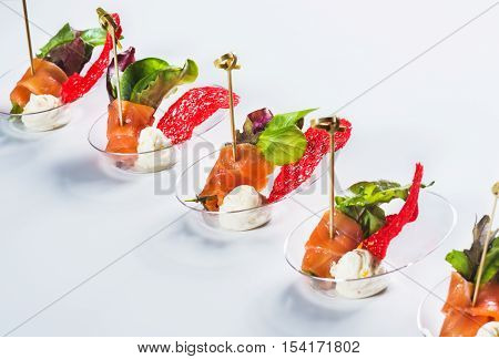 Salmon snack with soft cheese fresh salad and basil on light background