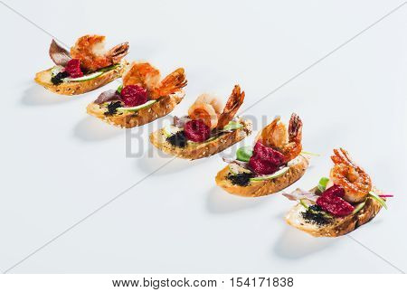 Bruschettas with grilled shrimp and mashed vegetables on light background
