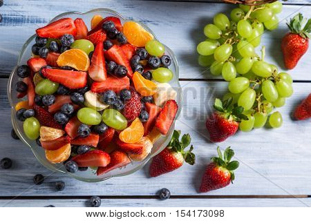Tasty spring fruit salad on old wooden table