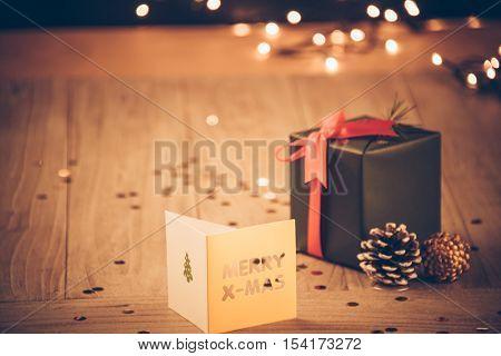 studio shot of christmas card and present on wood.