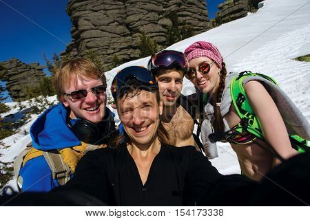 Group of happy friends snowboarding doing selfie at winter resort