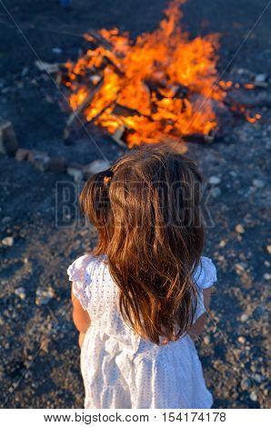 Little Jewish girl stand beside bonfire celebrate Lag BaOmer Jewish Holiday.