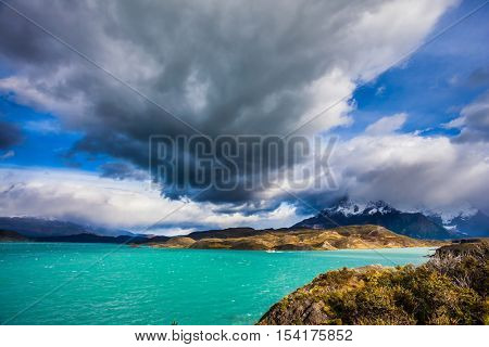 A giant cloud over the picturesque lake Pehoe. Concept of ecotourism. Chile, Patagonia. Torres del Paine National Park - Biosphere Reserve
