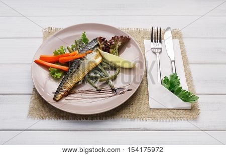 Restaurant food closeup on white wood background. Smoked mackerel with vegetables and parsley on round plate with cutlery. Appetizing fish dish, dinner meal. POV