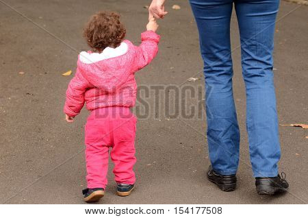 Child Hold Hands And Walks In The Park With His Mother