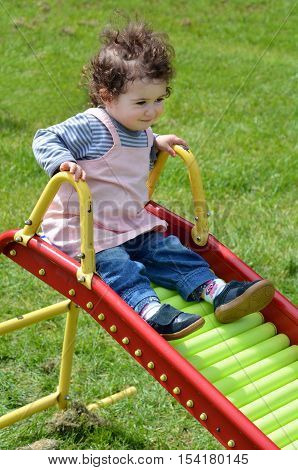 Little child (girl age 1-2) sliding on a slide in a home playground.