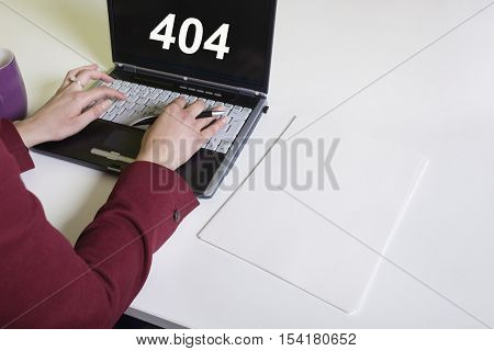 Close up of woman using laptop with text on the screen saying 404