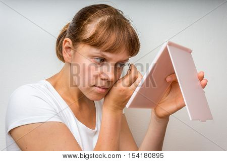 Woman Plucking Eyebrows With Tweezers In Front Of Mirror